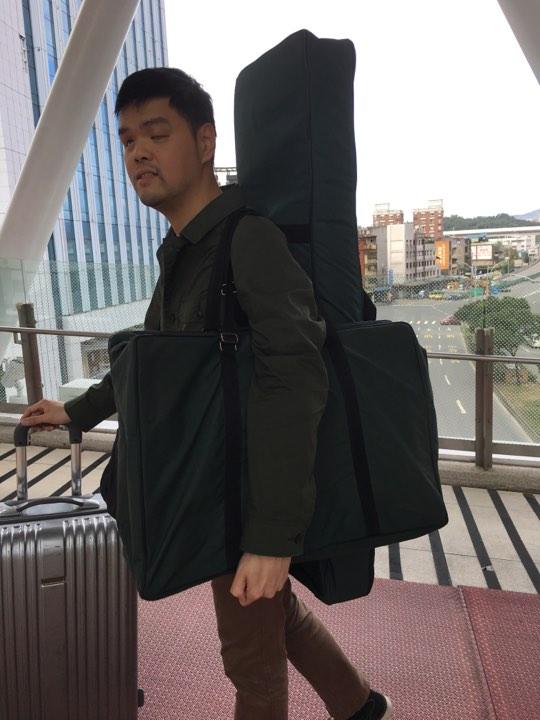 進發要出門演出了,且看他身上的裝扮。後面揹著的是小箏(小型古箏),掛在前胸的是箏架,手上推著的行李箱是喇叭,此外還要拿手杖。